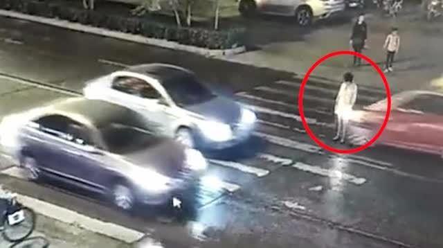 河南驻马店一女子被一辆红色出租车撞倒在斑马线上,期间多辆汽车和多名行人路过,无人将其扶起。一分钟后,倒地女子遭到另一辆汽车二次碾压。视频来源 @袁启聪